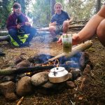 Über einem Lagerfeuer wird Tee gekocht.