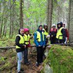 Junge Menschen stehen im Wald.