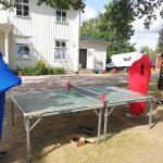 Junge Menschen in Tanzsäcken spielen Tischtennis.