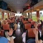 Ein Foto im Bus, den Mittelgang entlang. Auf den Sitzen junge Menschen die winken.