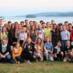 Ein Gruppenfoto mit jungen Menschen auf einer Wiese, im Hintergrund ein See.