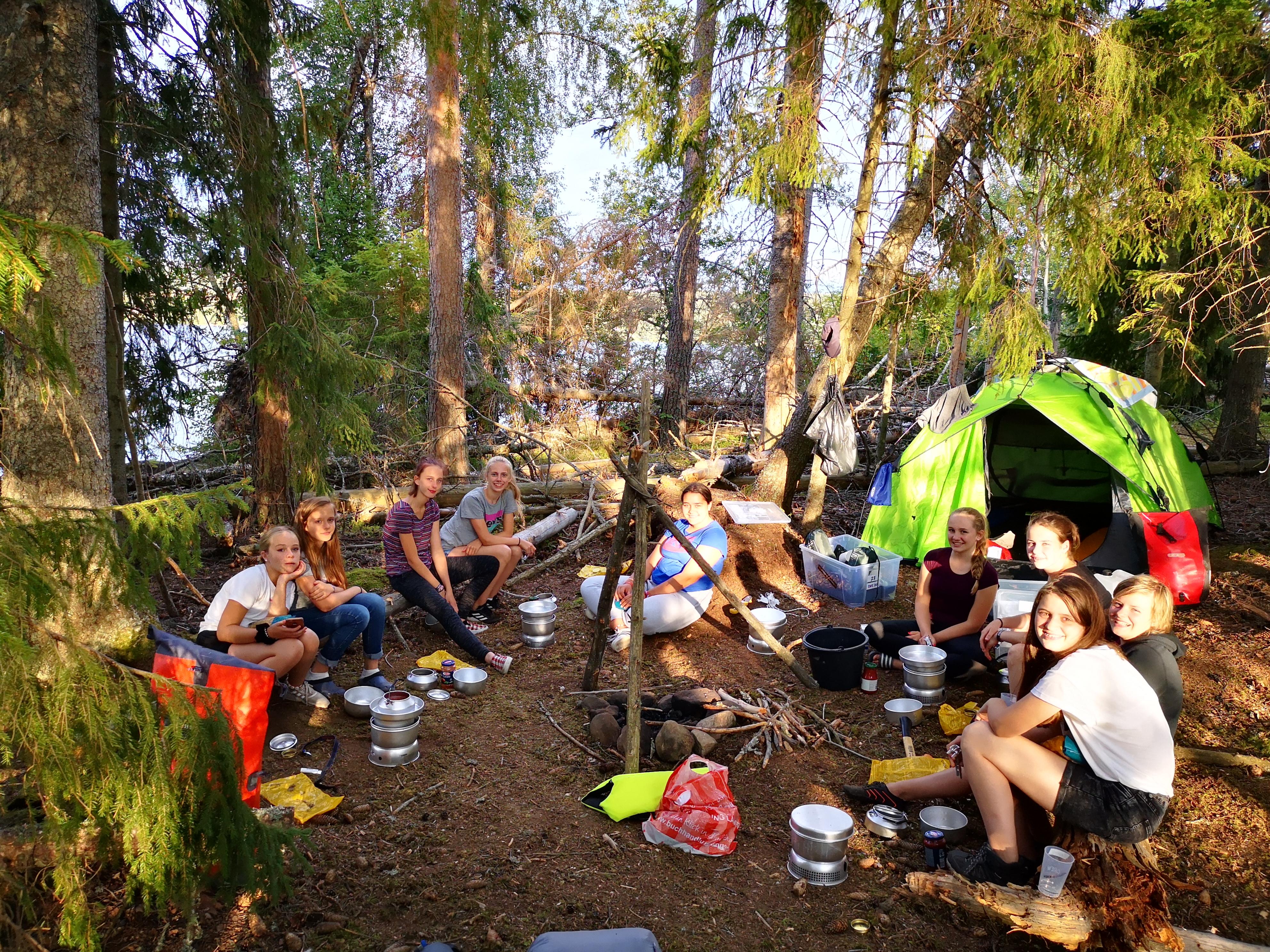 Jugendliche sitzen im Wald und kochen auf Campingkochern