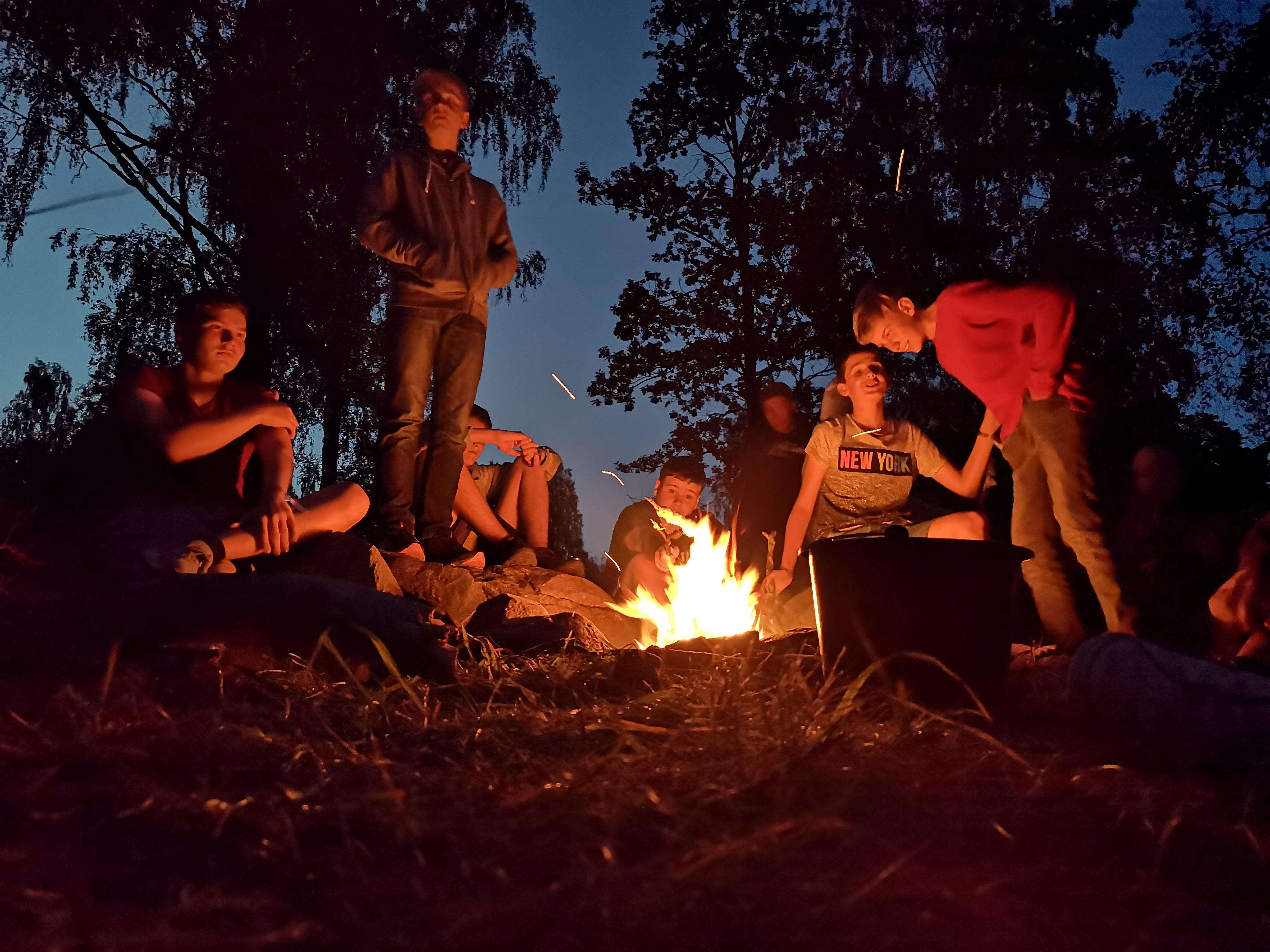 Jugendliche sitzen am Lagerfeuer