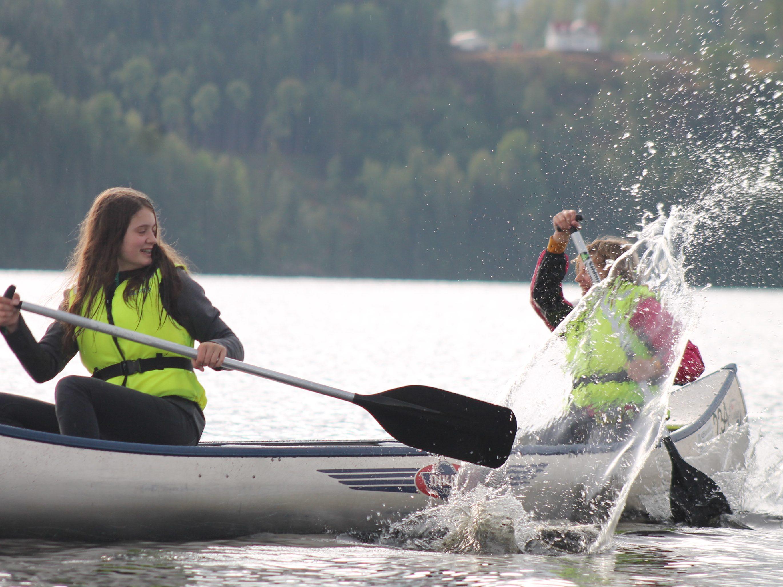 Zwei Mädchen sitzen im Kanu und spritzen mit Wasser