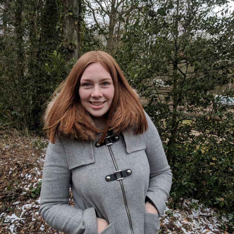 Portrait einer jungen Frau draußen vor grünem Hintergrund.