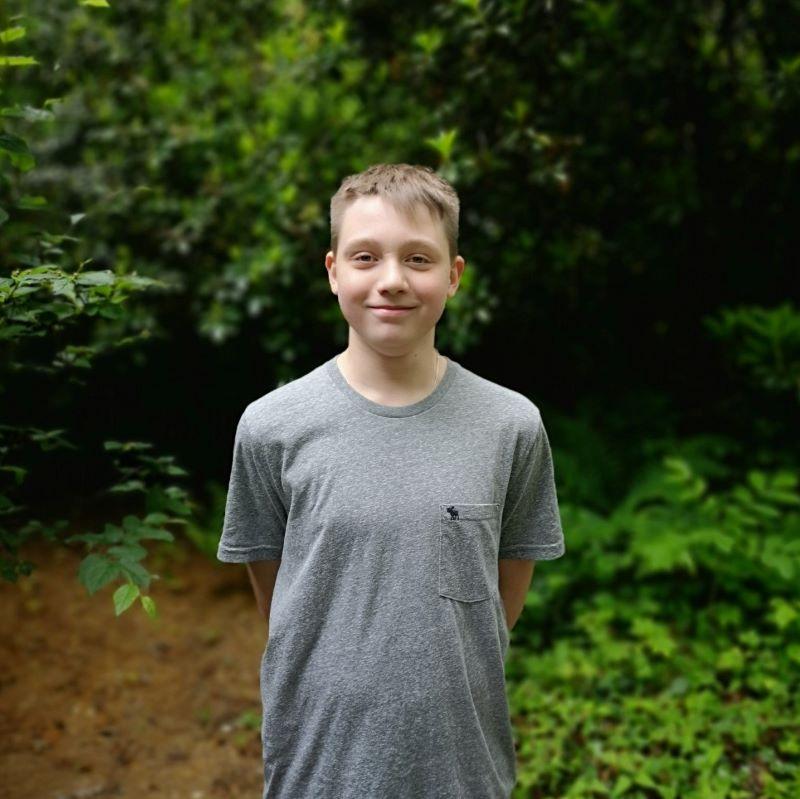 Portrait eines Teenagers draußen vor grünem Hintergrund.