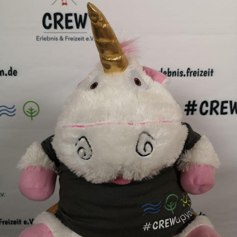 Ein Plüsch-Einhorn in einem CREW-Shirt vor einer CREW-Messewand.