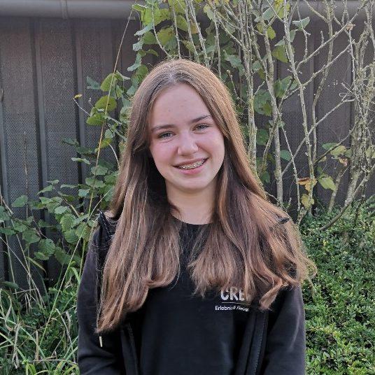 Eine Teenagerin draußen, im Hintergrund Pflanzen und eine Hauswand.