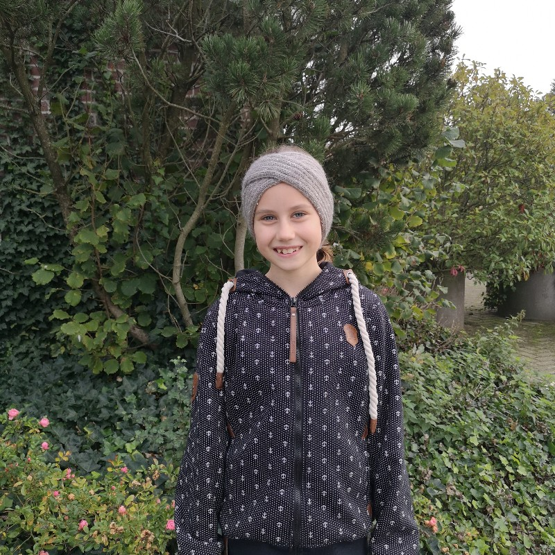 Eine Teenagerin, draußen, im Hintergrund Pflanzen.