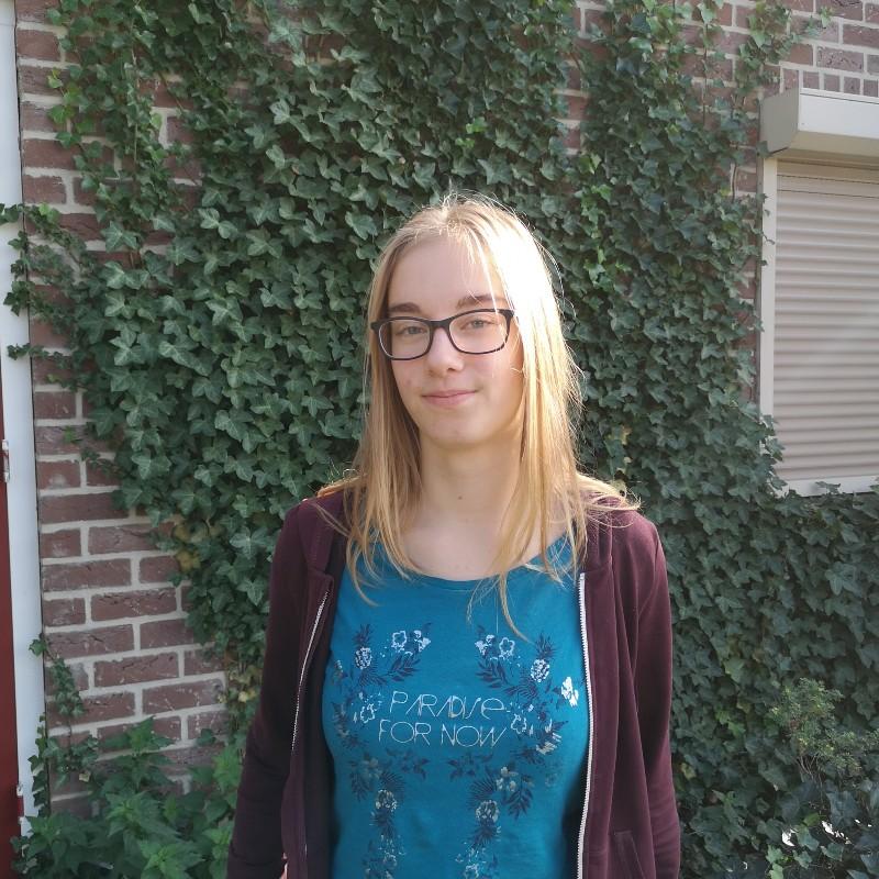 Eine junge Frau, draußen, im Hintergrund Pflanzen.