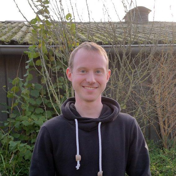 Ein Mann draußen, vor Pflanzen und einer Hauswand.