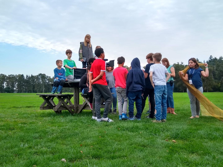 Kinder versammeln sich um Picknick-Tisch