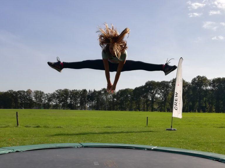 Mädchen springt auf Trampolin in den Spagat