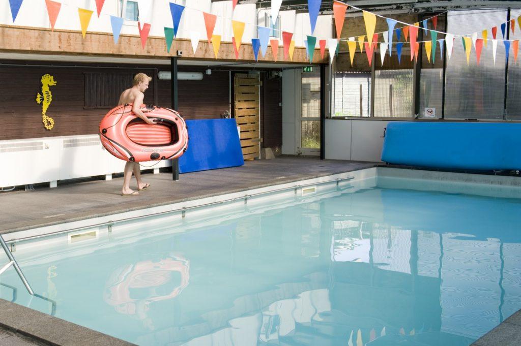 Junge mit Schlauchboot läuft an einem Schwimmbecken vorbei