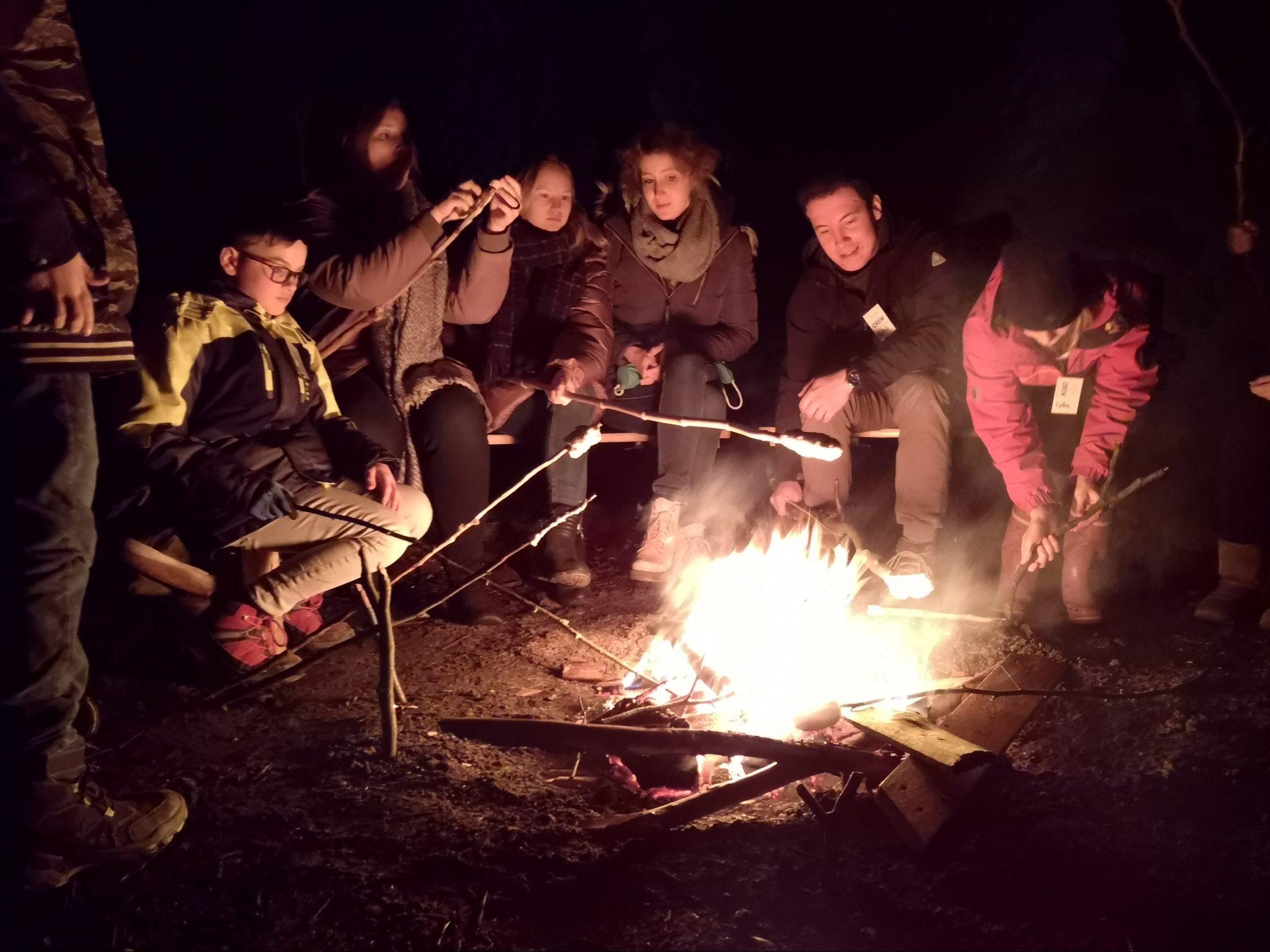 junge Menschen sitzen um ein Lagerfeuer und machen Stockbrot