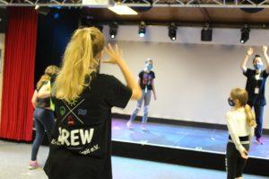 Mehrere junge Menschen tanzen mit Maske in einer großen Halle.