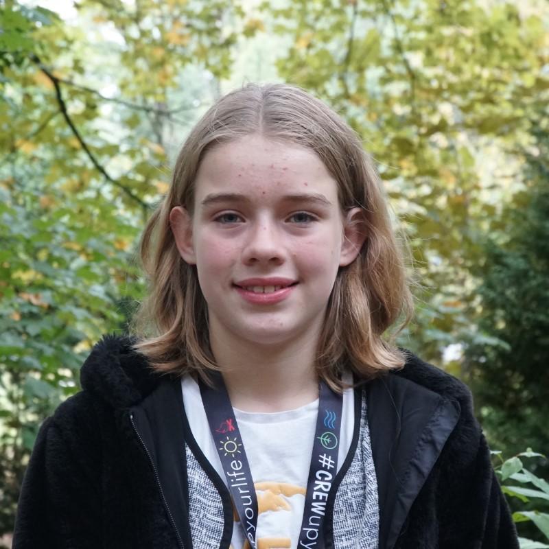 Das Portrait einer jungen Frau, im Hintergrund Blätter.