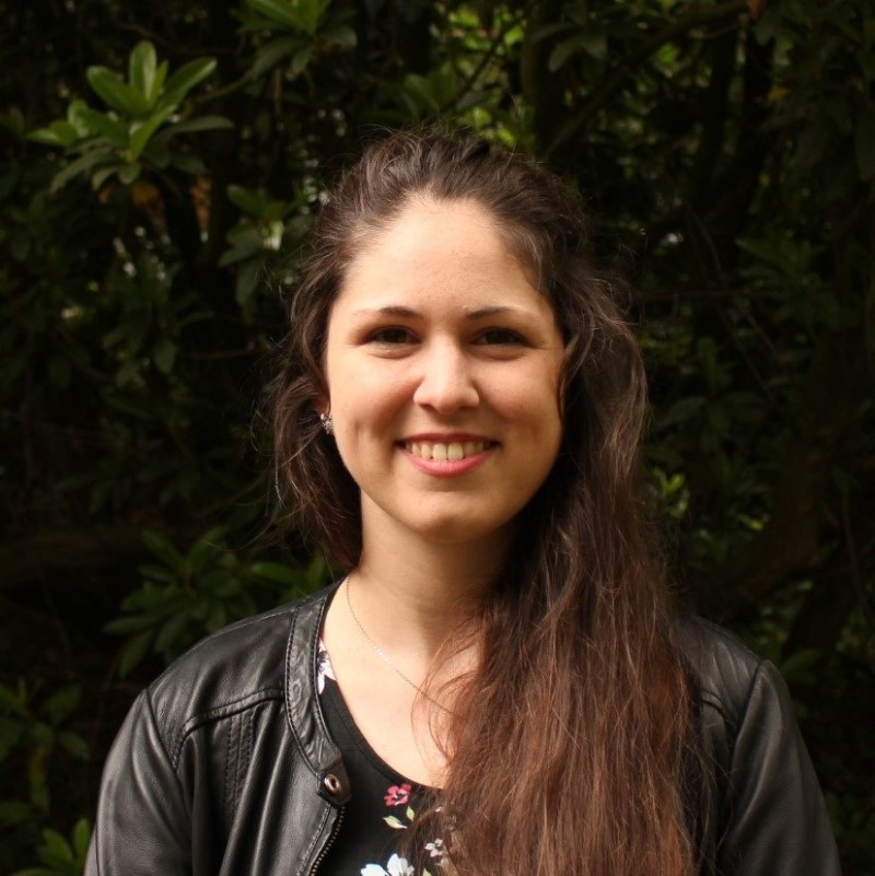Das Portrait einer jungen Frau vor einem Baum.