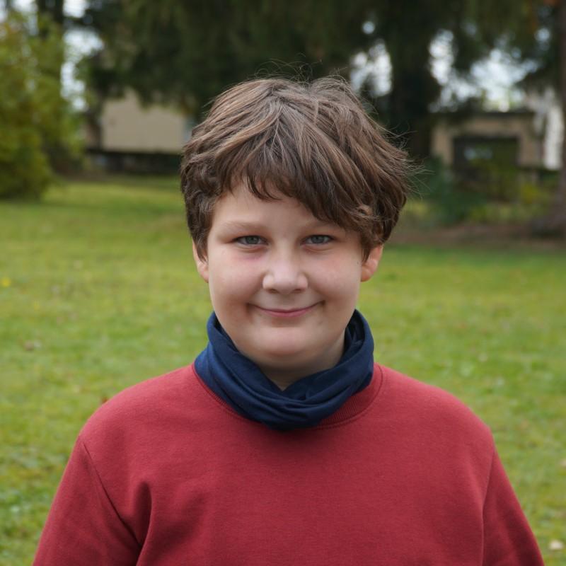 Das Portrait eines Teenagers vor einer Wiese.