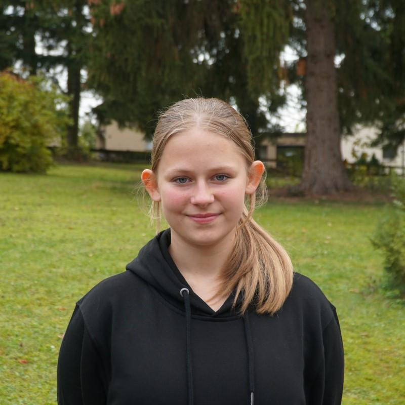 Das Portrait einer Teenagerin vor einer Wiese.