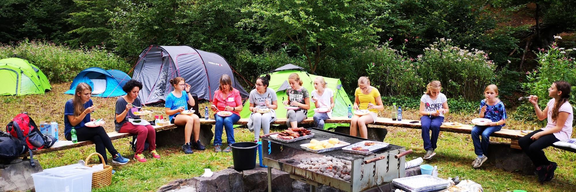 Kinder Sitzen auf einer Bank auf einem Zeltplatz und essen