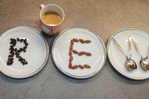 Buchstaben aus Nüssen und Rosinen auf Tellern