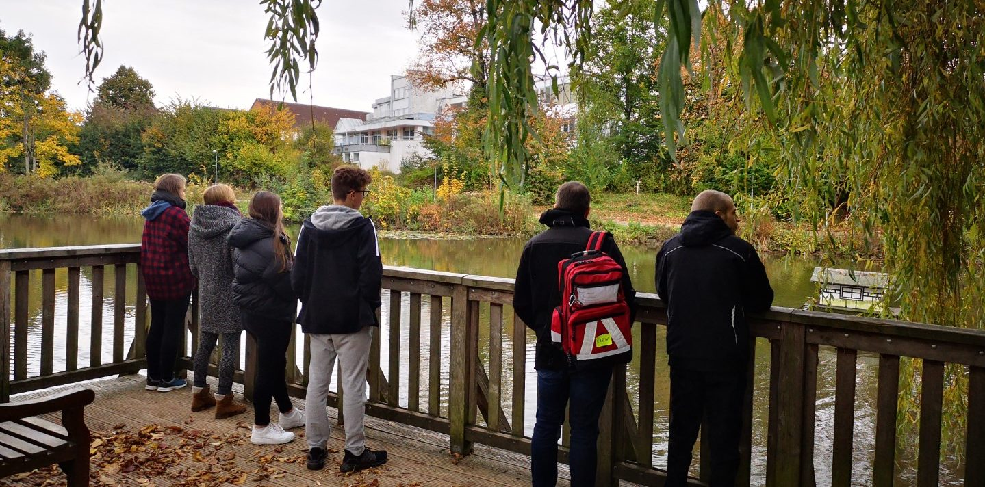 junge Menschen blicken auf einen See