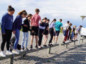 Jugendliche balancieren auf einem Balken